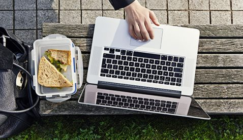 31 Oct 2014 --- woman eating a sandwich lunch and working on her computer in park. --- Image by © Alex Macro/Corbis