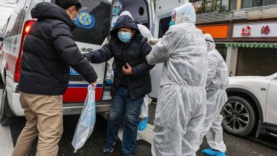 Persona scende da ambulanza con mascherina e persone accanto che l'aiutano