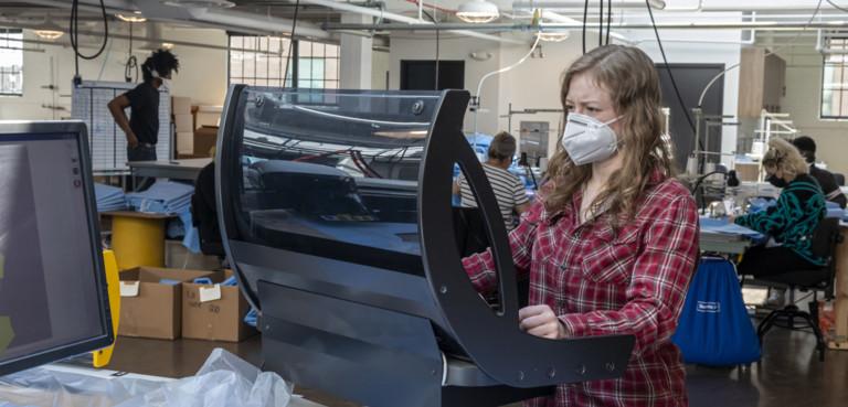 Donna a lavoro in fabbrica con la mascherina