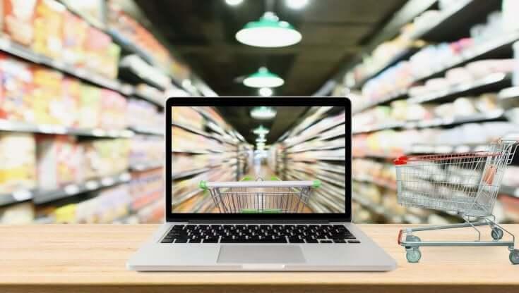 Immagine esplicativa con Pc poggiato su un tavolo con accanto un carrello della spesa in miniatura e corsia di supermercato in sottofondo