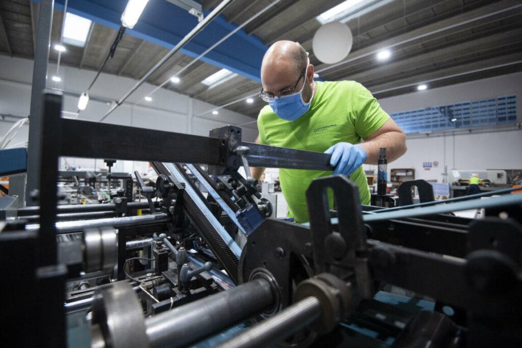 Operaio con mascherina al lavoro in fabbrica in una foto