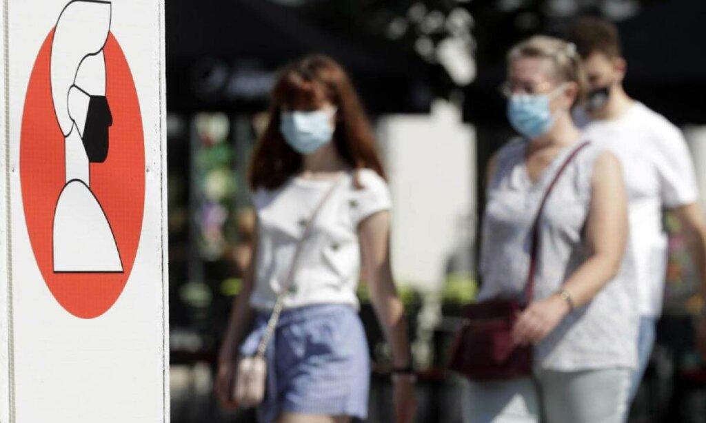 Persone a spasso in città con mascherine chirurgiche