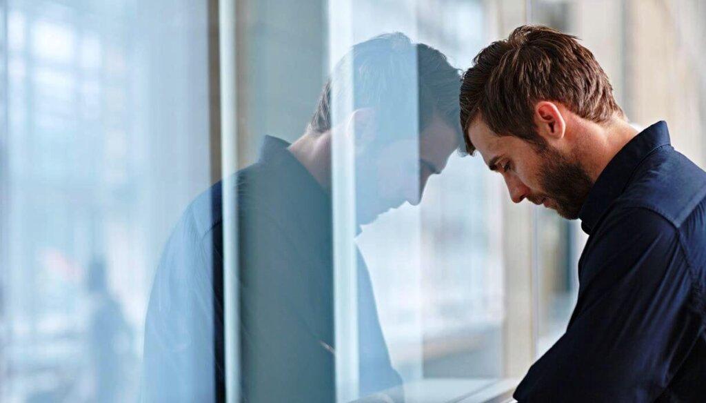 Uomo che appoggia la testa su una finestra